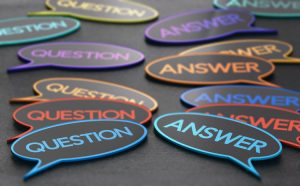 "Piles of stickers of different colors that say ""question"" and ""answer' on them."